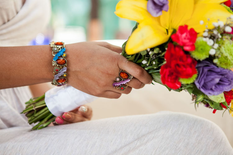 Midsection of bride holding colorful bouquet