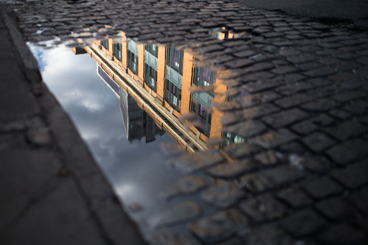High Angle View Of Building Reflecting In Puddle
