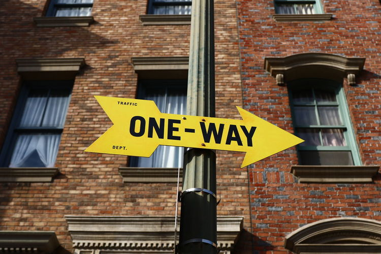 Low Angle View Of One Way Sign Outside Building