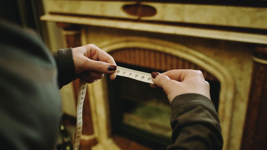 Cropped hands of woman holding tape measure against fireplace