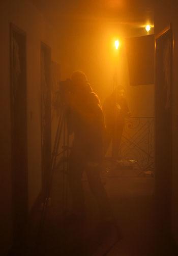 Adult Camera - Photographic Equipment Filmaker Illuminated Indoors  Leisure Activity Lifestyles Light Light And Shadow Lighting Equipment Men Night Orange Color People Production Real People