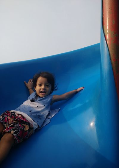 Portrait of cute girl playing on slide