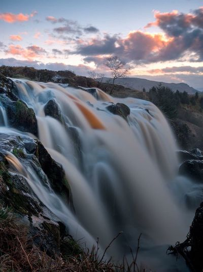 Scenic view of waterfall against cloudy sky