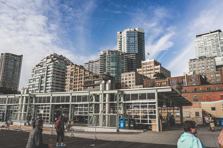 People on modern buildings in city against sky