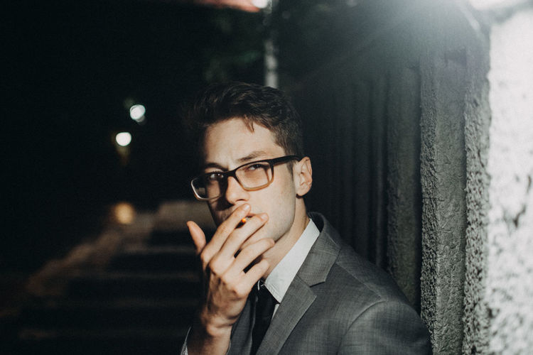 Portrait Of Businessman Smoking Cigarette By Illuminated Wall At Night