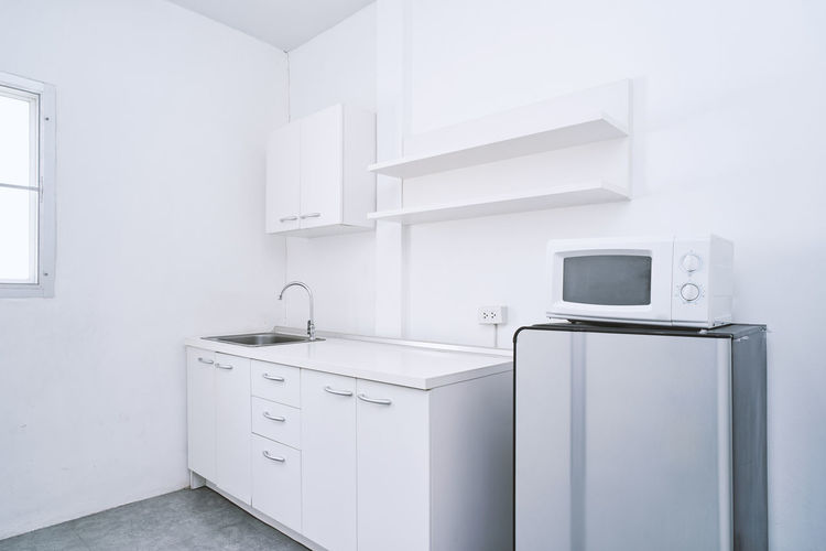 Modern living concept, White clean kitchen room with built-in furniture decoration ideas with water sink, storage, cabinet, shelf, refrigerator and microwave mock-up Decor Decorating Designs Living Modern Renovation Road Sink Apartment Cabinet Clean Contemporary Decoration Furniture Hotel Ideas Kitchen Microwave Mockup Particular Refrigerator Shelf Simple Storage White