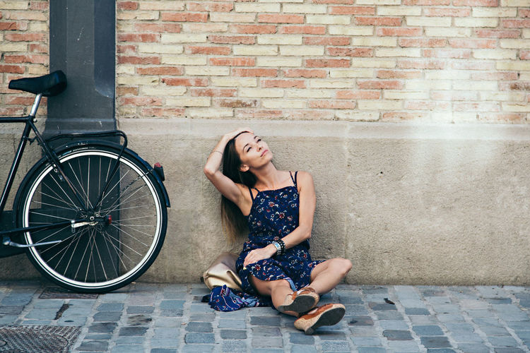 Adult Adults Only Bicycle Brick Wall City Day Full Length One Person One Woman Only One Young Woman Only Only Women Outdoors People Sitting Young Adult Young Women