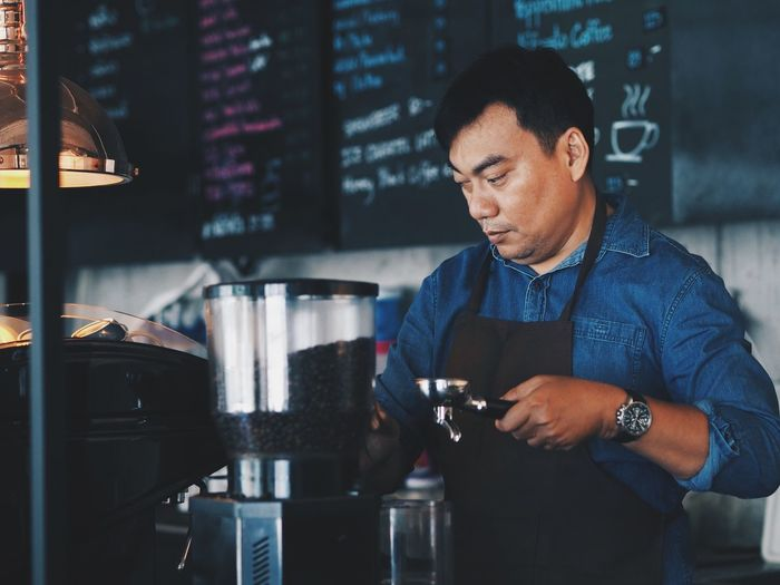 Smart barista making a coffee cup in coffee shop. Adult Alcohol Bar Counter Barista Bartender Business Coffee Coffee - Drink Coffee Maker Coffee Shop Drink Food And Drink Food And Drink Industry Glass Holding Indoors  Occupation One Person Preparation  Real People Refreshment Serving Food And Drinks Small Business Standing Working