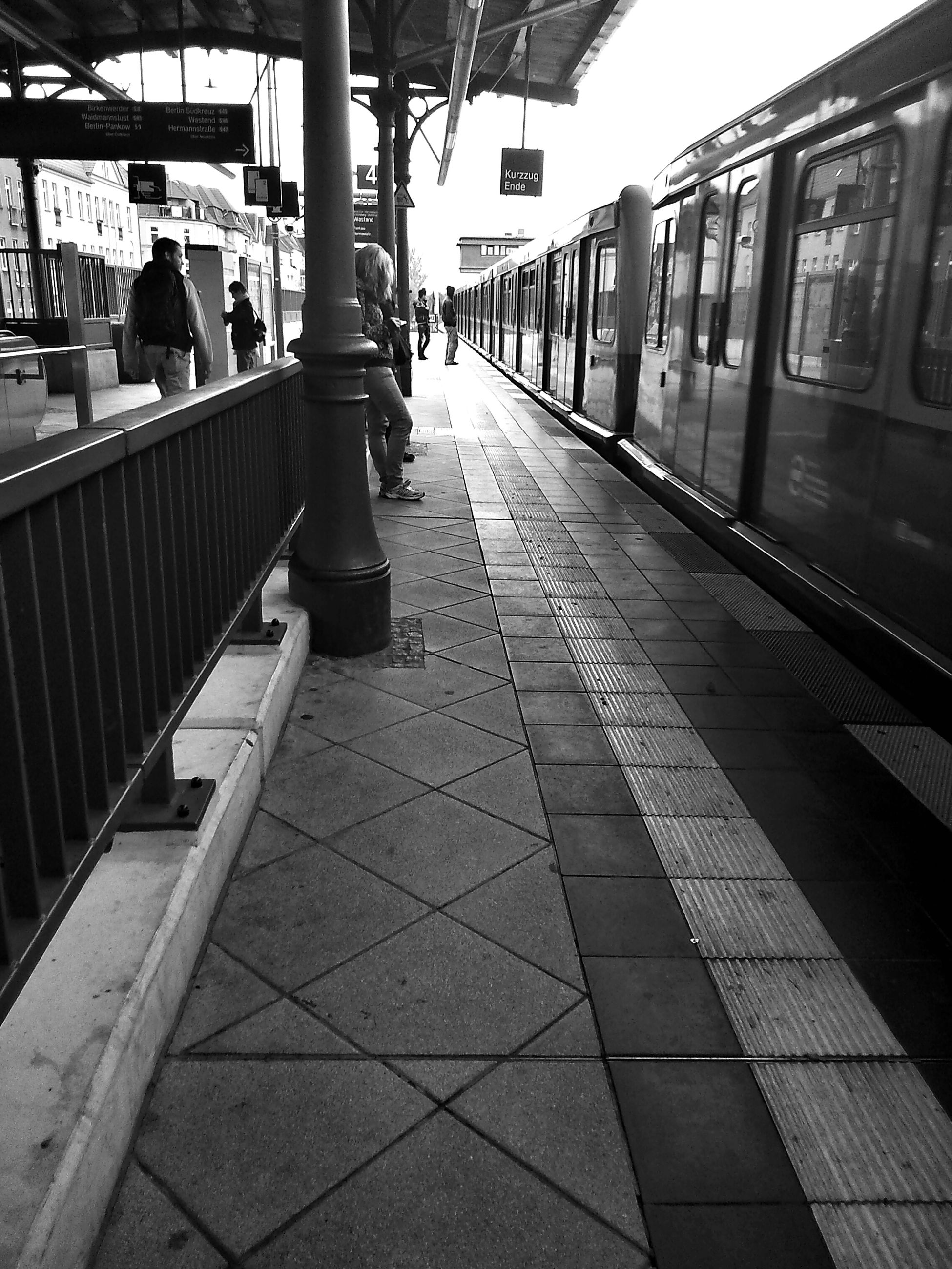 built structure, architecture, railroad station platform, railroad station, railroad track, public transportation, rail transportation, transportation, the way forward, incidental people, travel, building exterior, railing, empty, tiled floor, city life, indoors, public transport, city