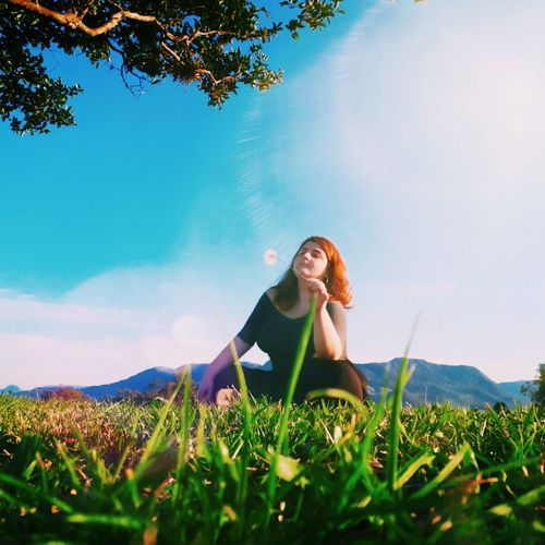 Low angle view of woman sitting on grassy land against sky