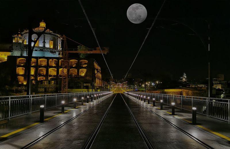 Illuminated light trails on bridge against sky at night