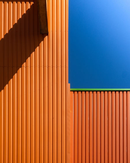 Close-up of orange building against clear blue sky