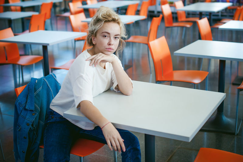 Portrait Of Young Woman Sitting On Chair In Classroom