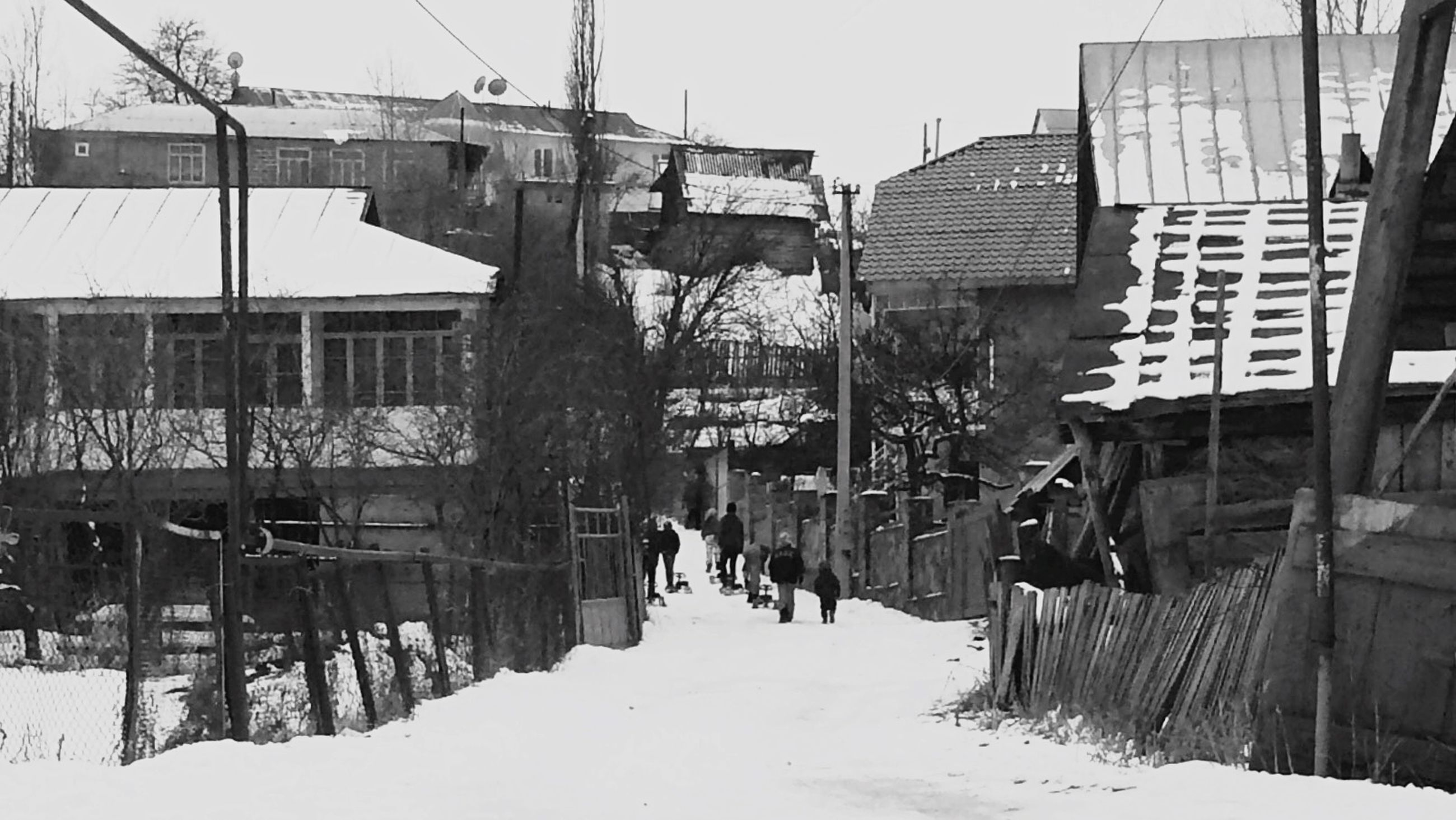 built structure, architecture, building exterior, snow, winter, cold temperature, season, house, sky, day, men, outdoors, covering, weather, residential structure, walking, incidental people, city, street