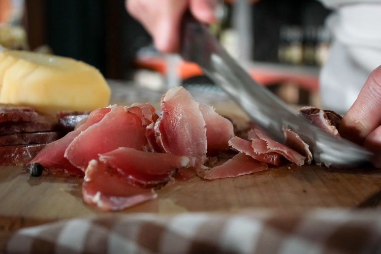 Cropped Image Of Hand Cutting Meat In Kitchen