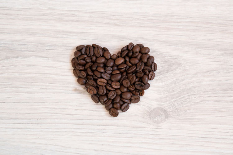 heart shape made out of coffee beans Beverage Coffee Aroma Brown Close-up Coffee Bean Directly Above Food Food And Drink Freshness Heart Shape High Angle View Indoors  No People Raw Coffee Bean Roasted Coffee Bean Table Wood - Material Wooden Texture