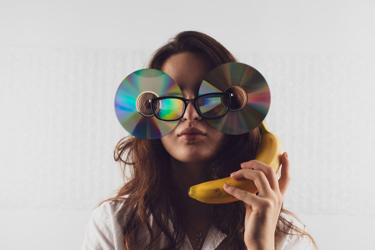 Woman wearing compact disc while holding banana