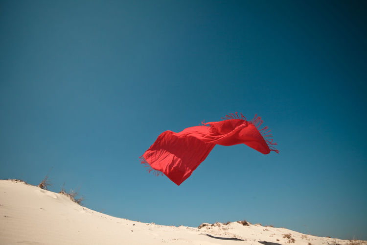 Low angle view of red scarf flying over sand against clear blue sky