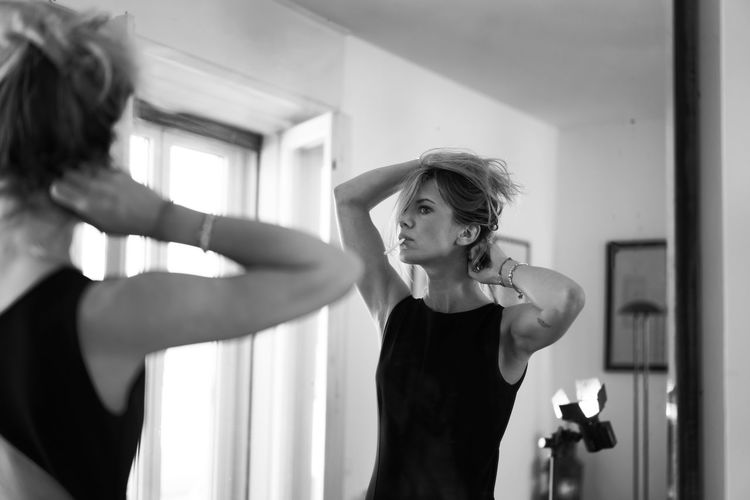 Woman holding cigarette while standing in front of mirror at home