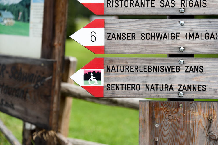 Close-up of information sign on wooden post