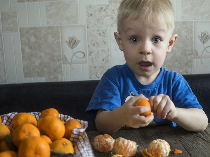 Surprised Boy Having Oranges While Sitting On Sofa At Home