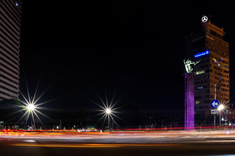 Light trails on street against illuminated buildings at night