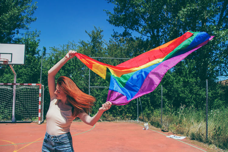 Young woman holding rainbow flag on basketball court against trees