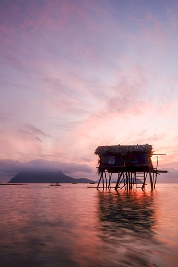 Stilt structure at calm sea against scenic sky