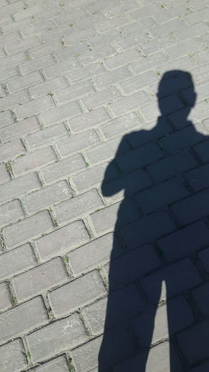 Shadow of man on footpath
