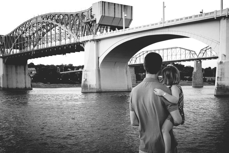 Rear View Of Man Holding Daughter Standing In Front Of Bridges Over Tennessee River
