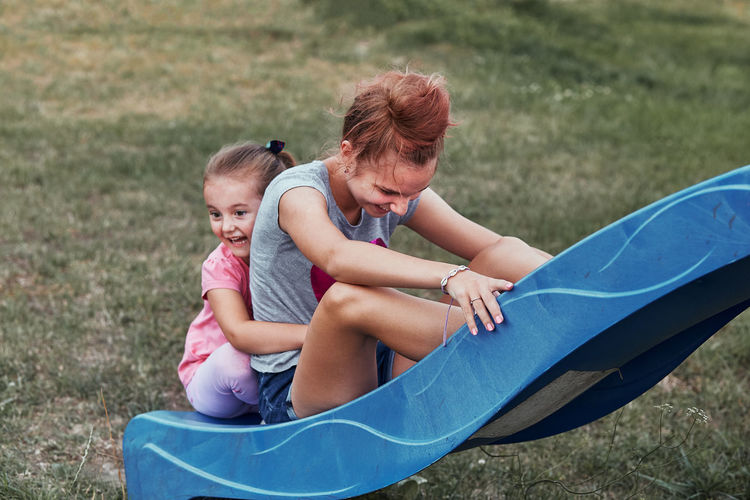 Siblings sitting on slide at playground