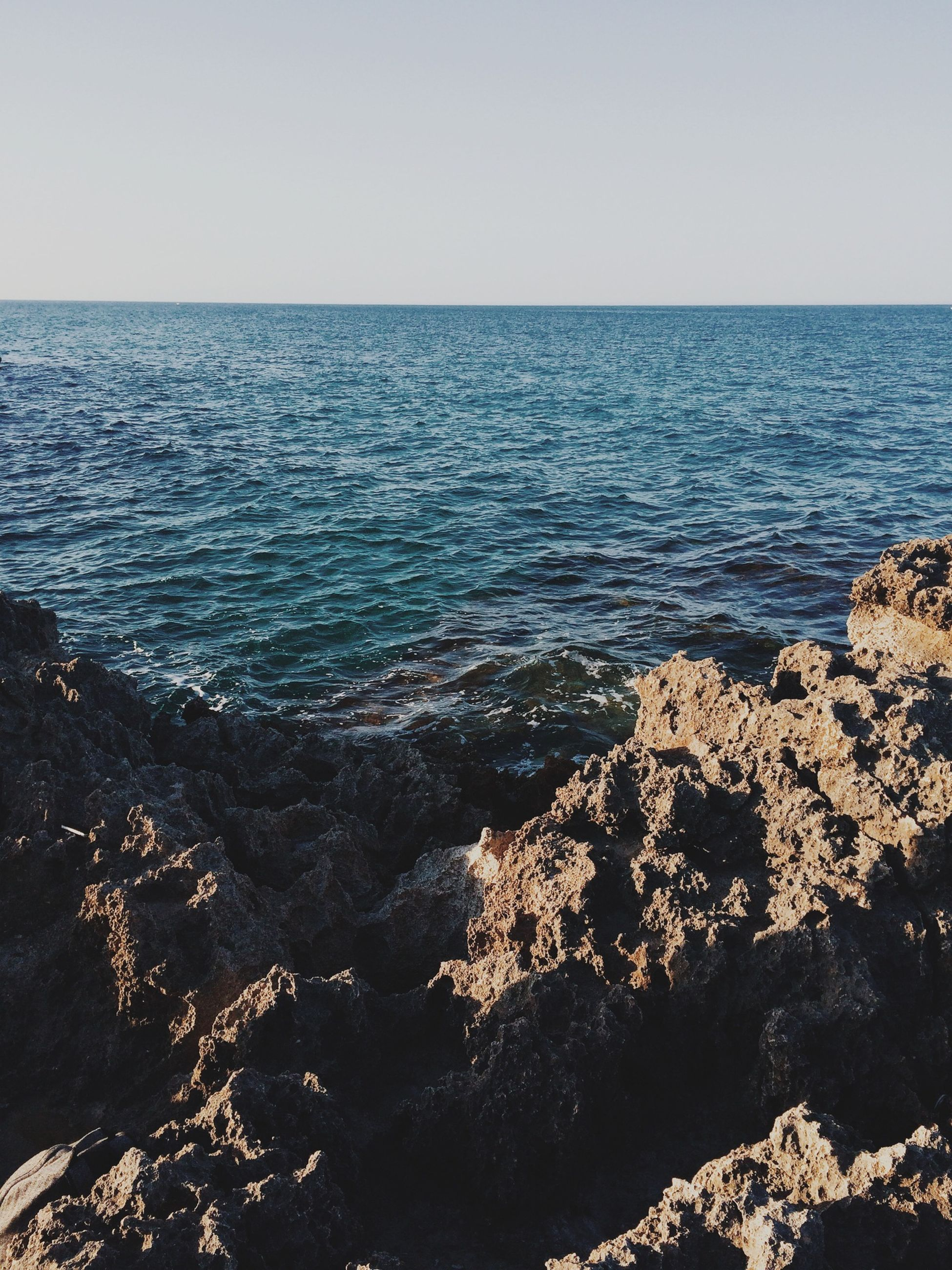 sea, water, horizon over water, scenics, tranquil scene, clear sky, beauty in nature, tranquility, nature, seascape, idyllic, rippled, blue, copy space, sky, outdoors, high angle view, no people, waterfront, day