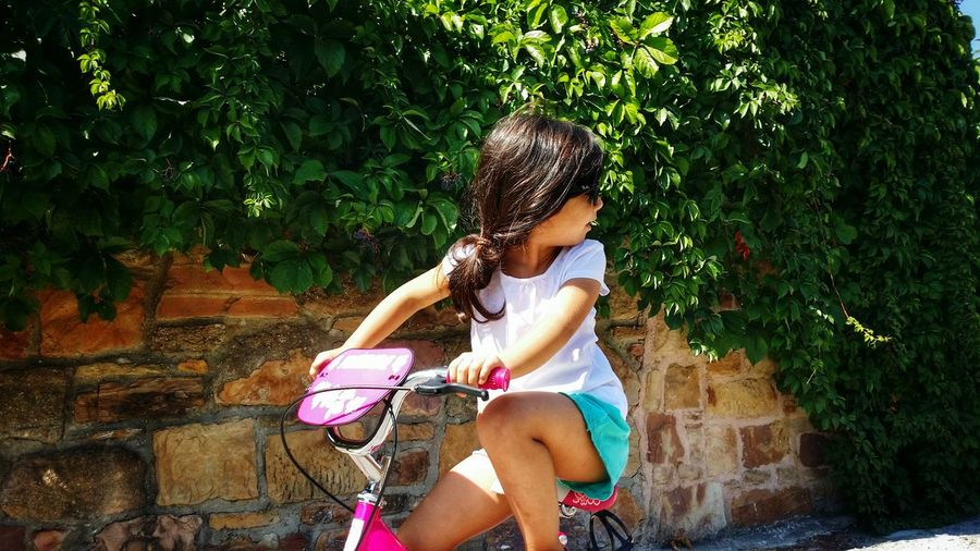 Little girl looking over shoulder while riding bicycle
