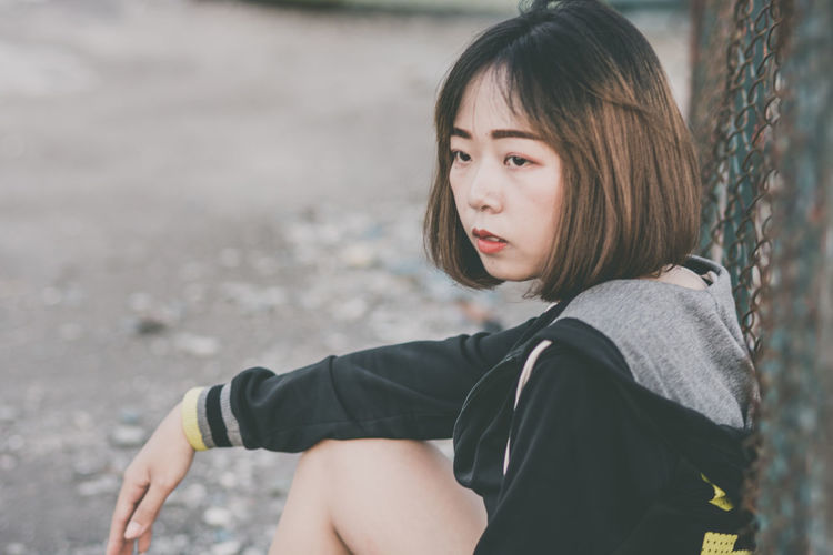 One Person Real People Leisure Activity Casual Clothing Lifestyles Sitting Hairstyle Looking Three Quarter Length Hair Day Women Looking Away Focus On Foreground Child Young Adult Girls Nature Contemplation Outdoors Bangs Beautiful Woman Teenager Innocence