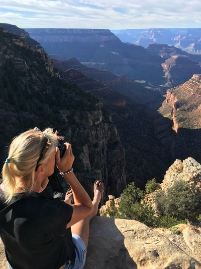 High angle view of woman photographing rocky mountains at grand canyon national park