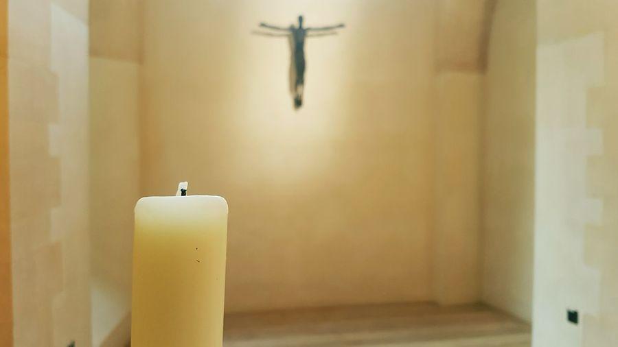 Candle against crucifix in church