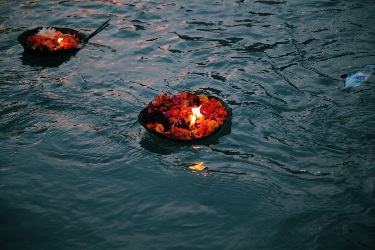 High angle view of religious offerings floating on water in ganges river