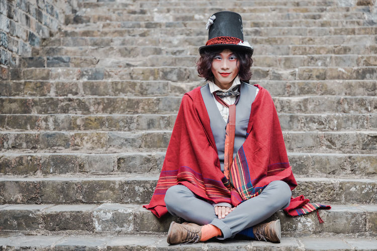 Portrait of man cosplaying mad hatter sitting on staircase against brick wall