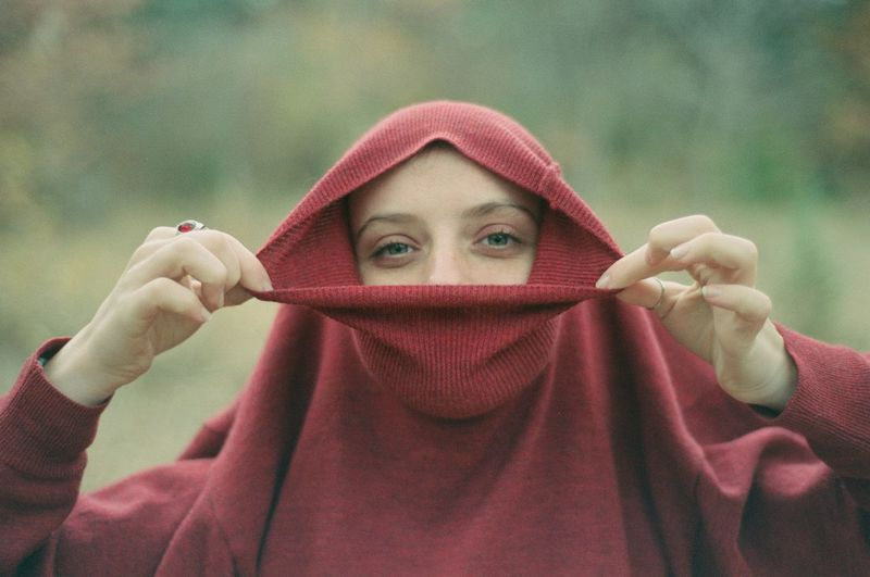 Portrait of young woman wearing hood outdoors
