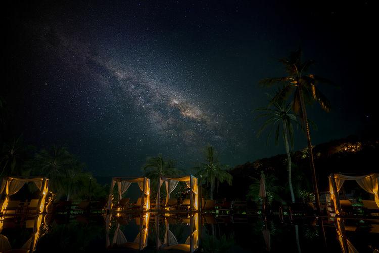 Reflection of gazebo in lake against sky at night