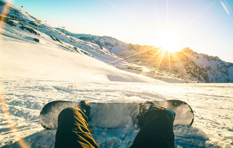 Low Section Of Man Snowboarding On Mountain During Sunny Day