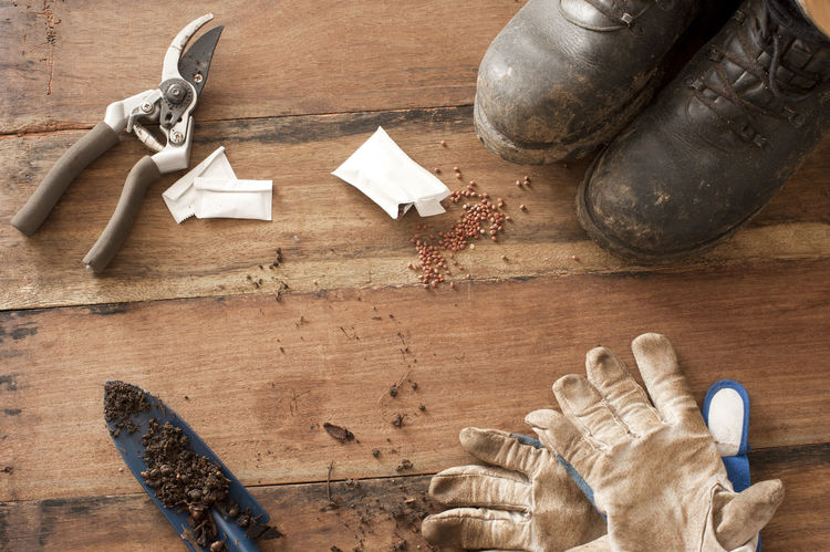 Gardening still life with old boots, secateurs, trowel and gloves displayed in the corners on a rustic wood background Backdrops Boots Gardener Gardening Gloves No People Secateurs Seeds Soil Still Life Trowel Wood Wooden