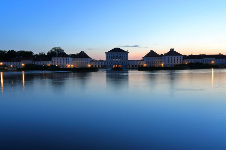 Buildings by lake against clear blue sky at dusk