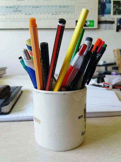 Pencils and pens in mug on table