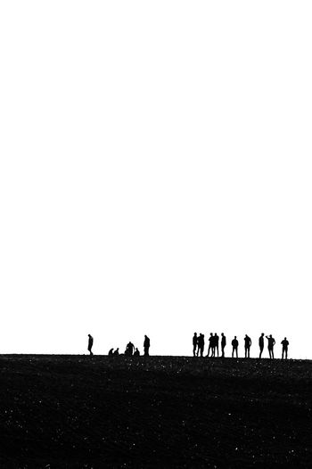 Silhouette people on field against clear sky