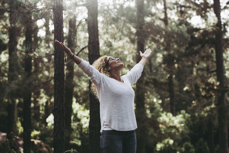 Rear view of woman with arms raised standing in forest
