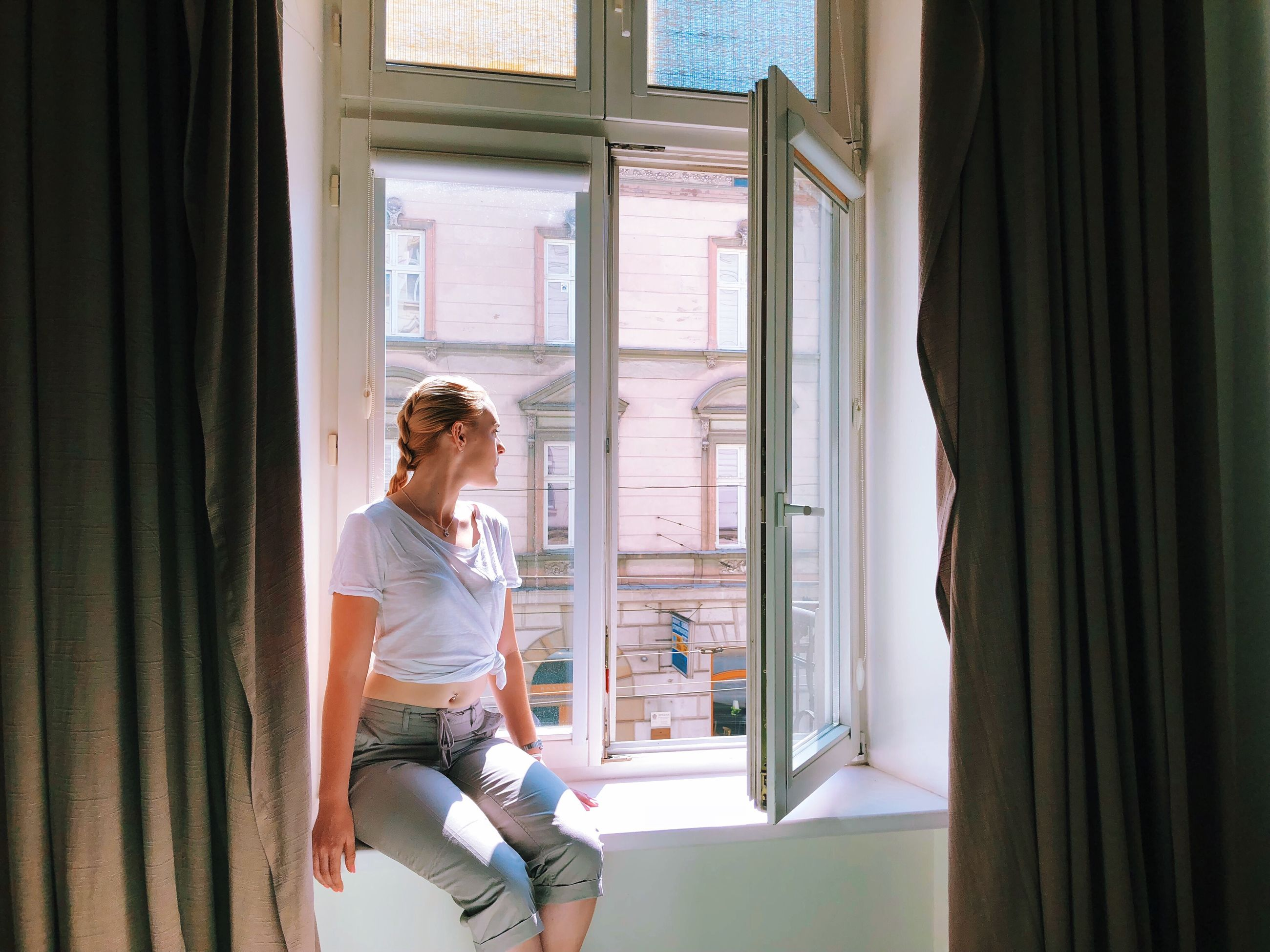 window, curtain, one person, casual clothing, real people, indoors, lifestyles, three quarter length, sitting, home interior, looking, adult, day, looking through window, women, young adult, leisure activity, young women, contemplation, hairstyle