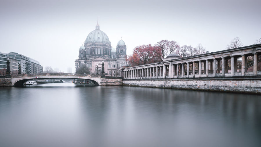 View of berlin cathedral by footbridge against sky
