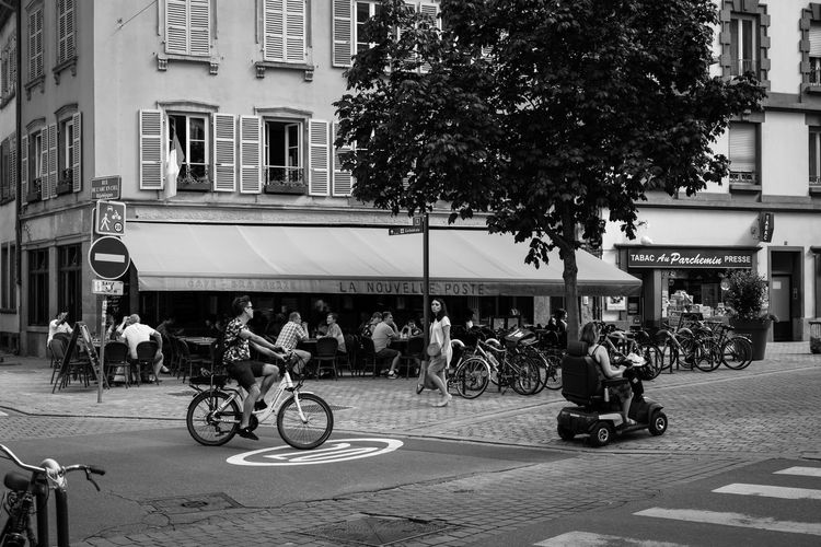 Streetlife ... Urban Perspectives Black & White Monochrome Street Photography Black And White Transportation Mode Of Transportation Architecture City Building Exterior Land Vehicle Bicycle Built Structure Tree Men Street Group Of People Real People Plant Road Women Lifestyles Large Group Of People Building Outdoors Riding The Street Photographer - 2019 EyeEm Awards