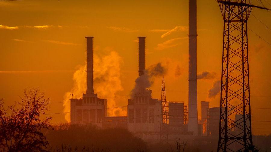 Smoke emitting from chimney against sky during sunset
